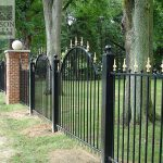 Traditional victorian style wrought iron security fence with polished brass post tops